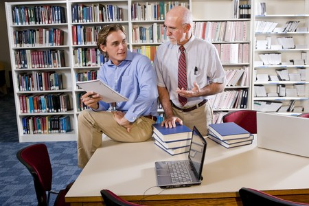 conversing: College professor with male student conversing in library