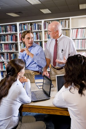 profesor: Profesor de colegio con un grupo diverso de estudiante hablando en biblioteca
