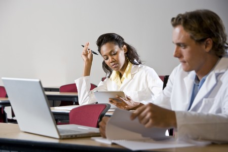 medical study: Multiracial medical students wearing lab coats studying in classroom Stock Photo