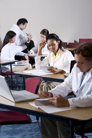 Tudiants en médecine pluriraciale portait les manteaux de laboratoire étudier en salle de classe  Banque d'images - 7159175