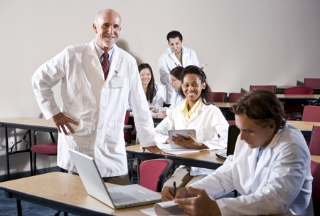 Professor with medical students wearing lab coats in classroom photo