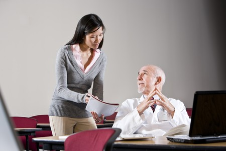 Doctor and female assistant in conference room looking at notebook Stock Photo - 7159167
