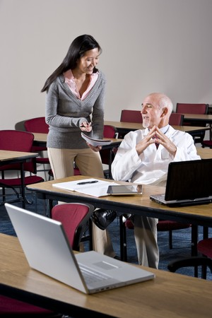 Doctor and female assistant in conference room looking at notebook Stock Photo - 7159201