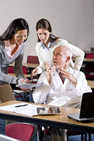 Scientist in lab coat talking to assistants in conference room Stock Photo - 7159227