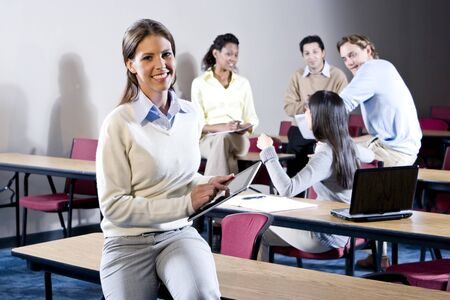 College students in classroom talking, focus on woman in foreground photo