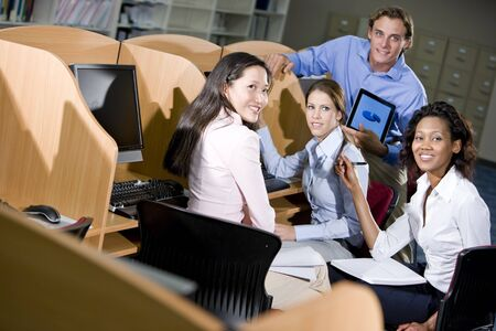 Diverse university students sitting  at library computer studying together Stock Photo - 7159195