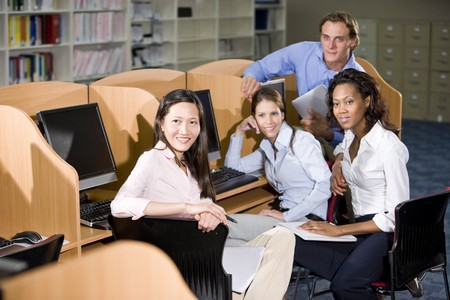 Diverse university students sitting  at library computer studying together photo