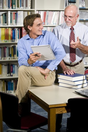 university professor: Mature university professor and male student talking in library Stock Photo