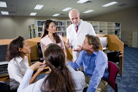 university professor: Multiracial university students with professor conversing in library Stock Photo