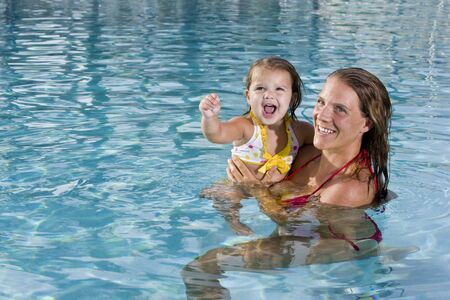 Mother and 2 year old daughter enjoying swimming pool photo