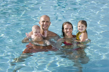 Portrait of young family with baby and toddler smiling in swimming pool photo