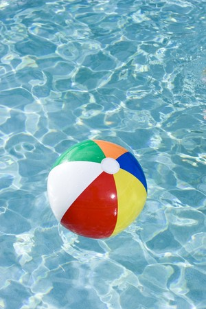 Colorful beach ball floating on surface of swimming pool water photo