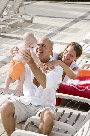 Young family on vacation, relaxing on pool deck lounge chairs photo