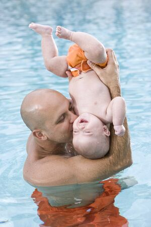 Loving father and baby having fun upside down in swimming pool photo