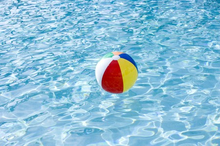 colorful water surface: Beach ball floating on surface of swimming pool water Stock Photo