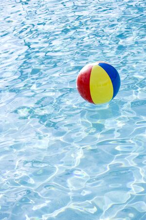 Beach ball floating on surface of swimming pool water photo