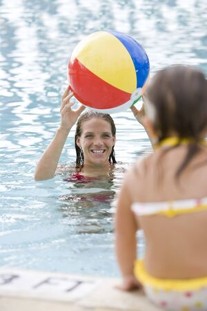 Mother and 2 year old daughter playing with beach ball in pool photo