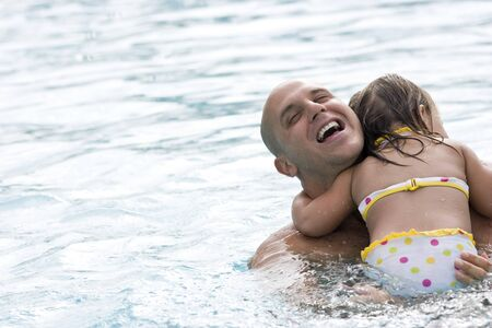 Father hugging 2 year old daughter in swimming pool photo