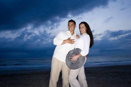 Happy mid-adult Hispanic couple smiling on beach at dawn Stock Photo - 7219899