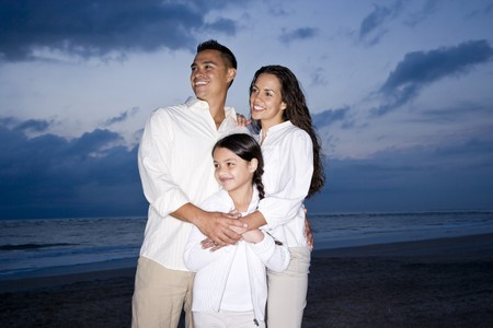 Happy mid-adult Hispanic family with 9 year old girl smiling on beach at dawn