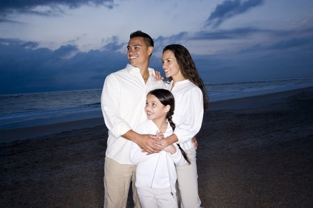 Happy mid-adult Hispanic family with 9 year old girl smiling on beach at dawn Stock Photo - 7219890