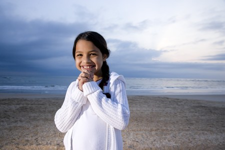 Cute 9 year old Hispanic girl smiling on beach at dawn photo