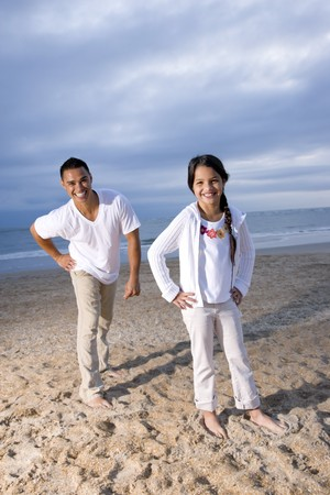 Hispanic father and 9 year old daughter having fun on beach smiling at camera photo