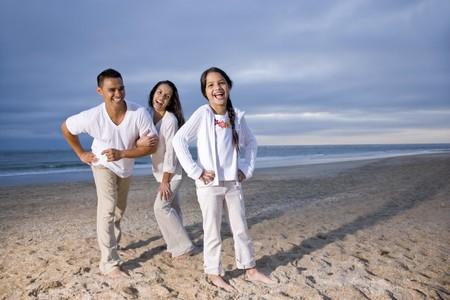 Hispanic family with 9 year old daughter having fun on beach photo