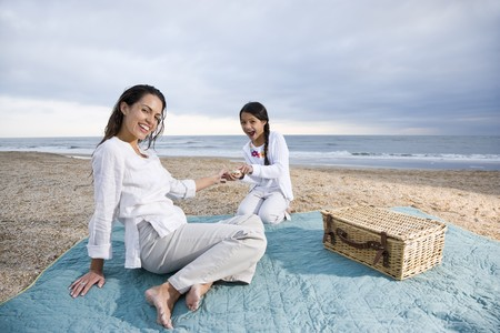 9 year old girl: Latin American mother and 9 year old girl having picnic on beach