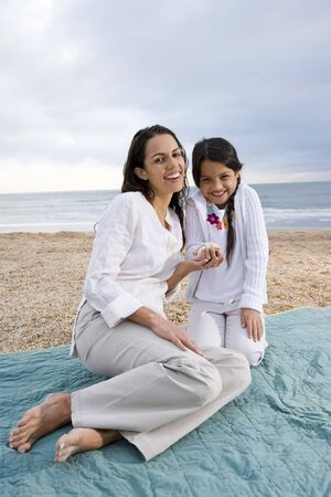 Latin American mother and 9 year old girl sitting on blanket at beach photo