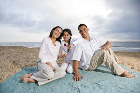 Latin American family with 9 year old girl sitting on blanket at beach Stock Photo - 7219916