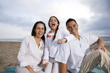 Latin American family with 9 year old girl sitting on blanket at beach Stock Photo - 7219908