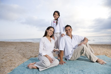 Latin American family with 9 year old girl sitting on blanket at beach photo