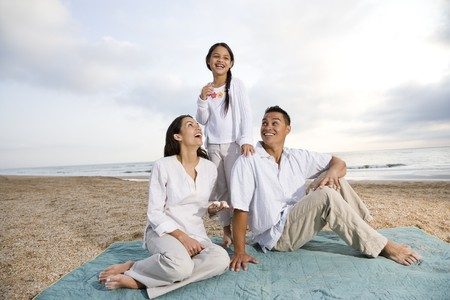 9 year old girl: Latin American family with 9 year old girl sitting on blanket at beach