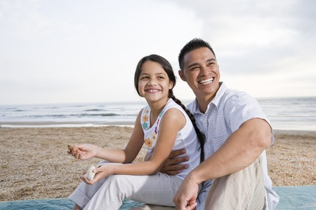Hispanic father and 9 year old daughter having fun at beach
