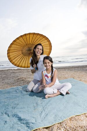 Hispanic mother and 9 year old daughter having fun at beach photo