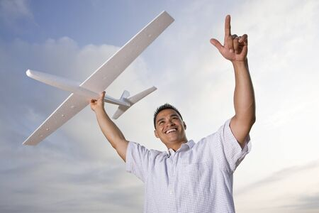 Smiling Hispanic man holding model airplane glider over head Stock Photo