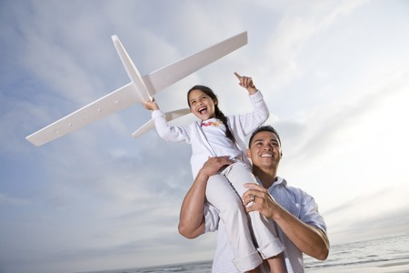 Hispanic dad and 9 year old child playing at beach with model plane photo