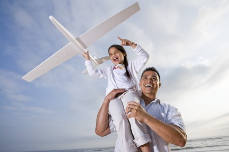 old plane: Hispanic dad and 9 year old child playing at beach with model plane