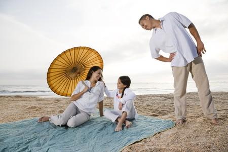 Hispanic family with 9 year old girl on beach blanket photo