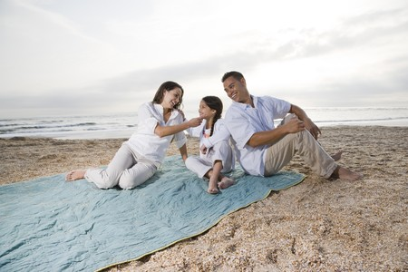 9 year old: Hispanic family with 9 year old girl on beach blanket