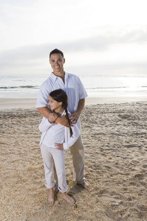 Hispanic father and 9 year old daughter standing together on beach photo