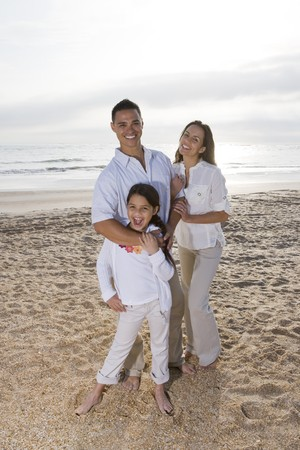 Hispanic family with 9 year old daughter standing on beach Stock Photo