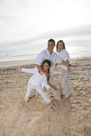 Hispanic family with 9 year old daughter having fun on beach photo
