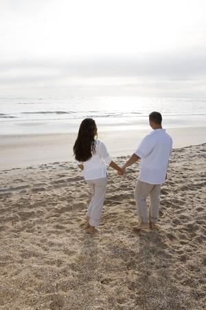 Romantic mid-adult Hispanic couple watching sunrise at beach photo