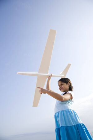 9 year old: Low angle view of pretty 9 year old Hispanic girl playing with toy model airplane