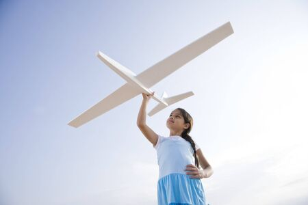 model airplane: Low angle view of pretty 9 year old Hispanic girl playing with toy model airplane