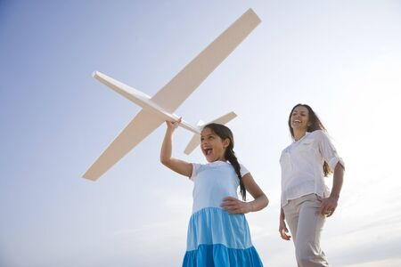 model airplane: Hispanic mother and 9 year old child having fun with toy plane