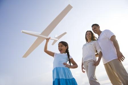 Hispanische familie en 9-jarige dochter met plezier met het vlieg tuig van speel goed  Stockfoto