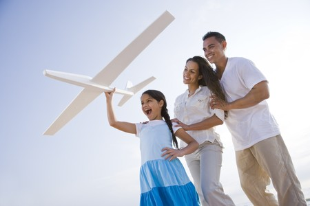 Hispanic family and 9 year old daughter having fun with toy plane Stock Photo - 7219840